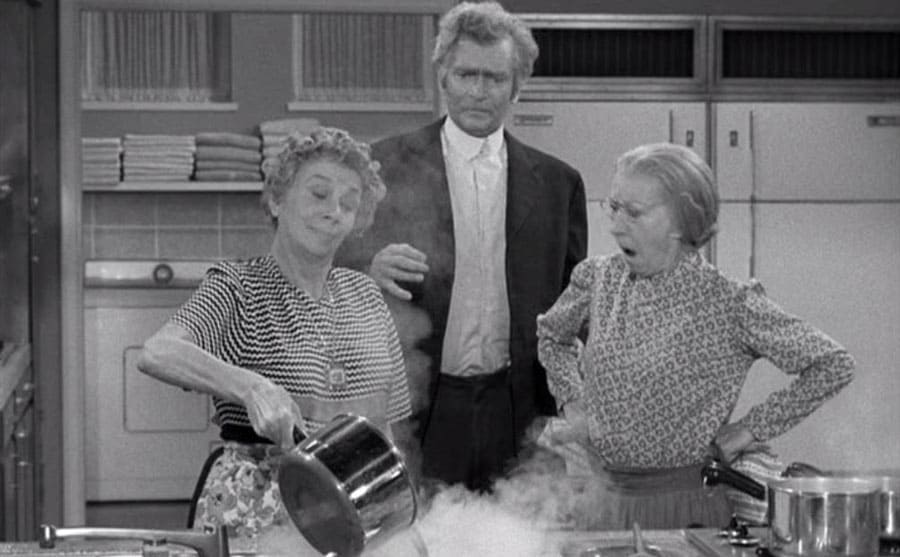 Granny's pot of boiling water is being poured into the sink, and she has an upset and shocked look on her face.