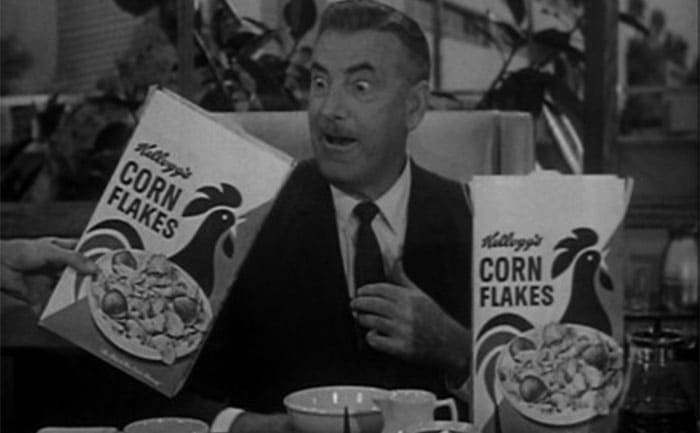 Raymond Bailey at his desk surrounded by Kelloggs Cornflakes