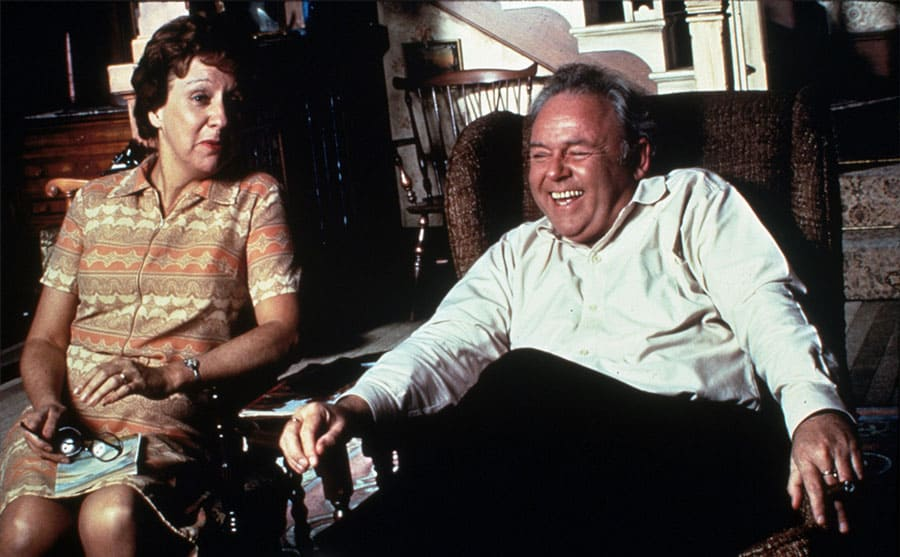 A scene from All in the Family with Carroll O'Connor and Jean Stapleton sitting in living room chairs