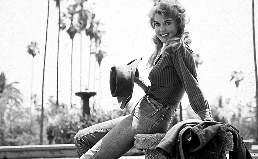 Donna Douglas as Elly May sitting with a hat and jacket near some steps