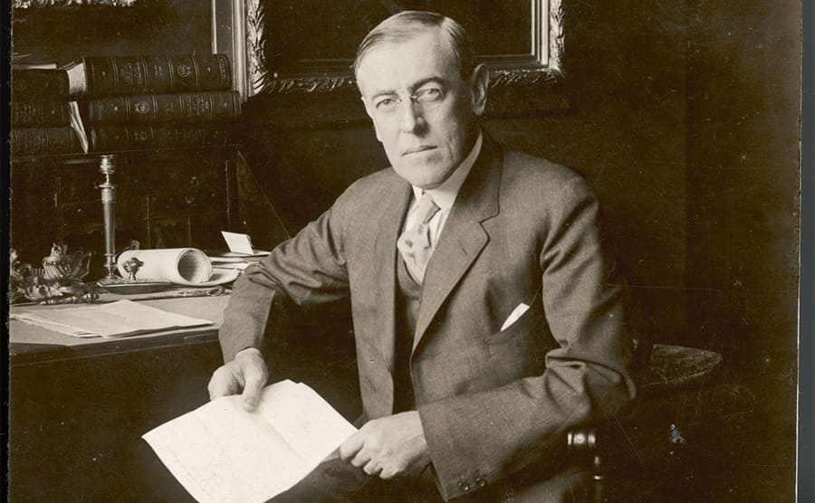 President Woodrow Wilson sitting at his desk holding papers