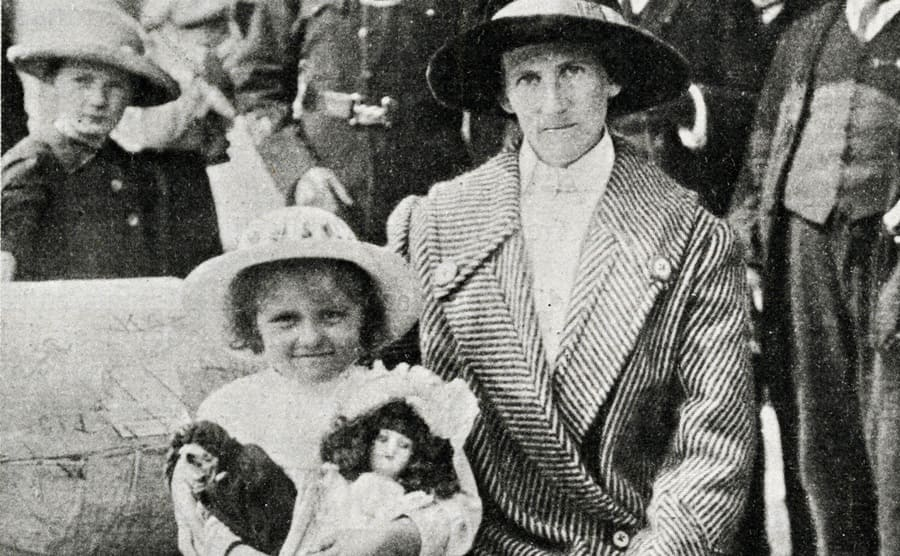 A little girl holding her dolls and sitting next to a woman