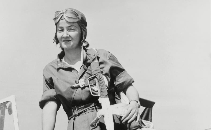 Nancy Harkness Love wearing a WASP uniform standing on an airplane wing with her parachute slung over her shoulder