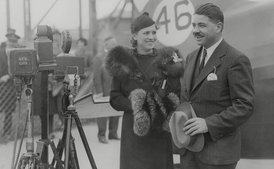 Jacqueline Cochran and Pilot Wesley Smith with cameras set up in front of them and a plane in the background