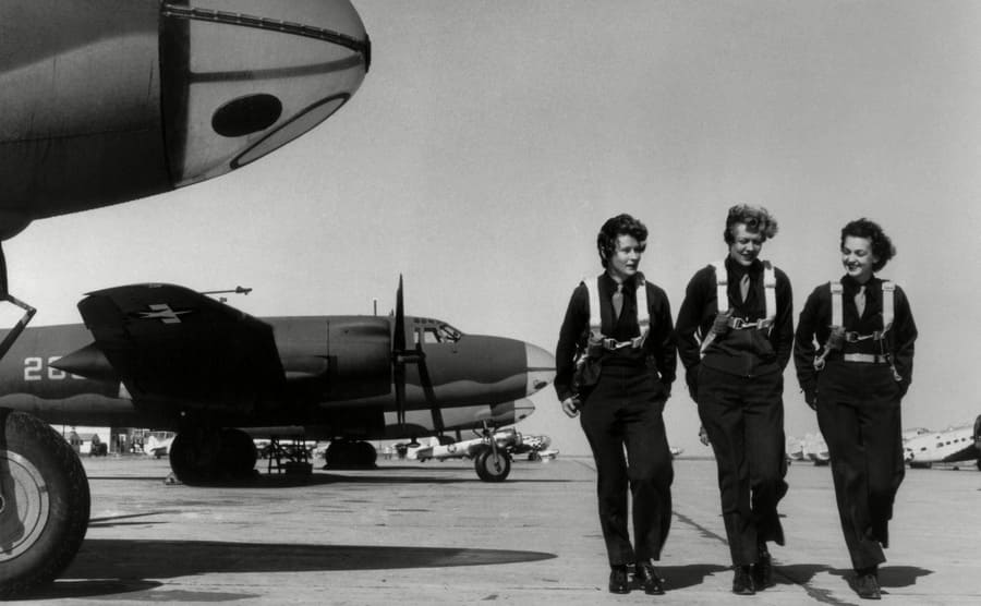 Three WASP pilots walking in a lot full of planes