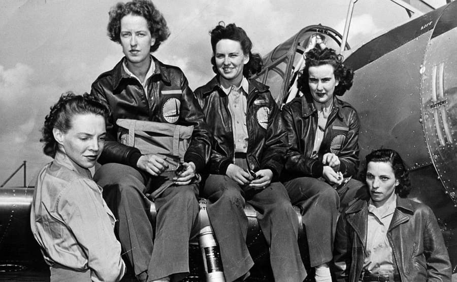 Cornelia Fort and four other pilots sitting and standing around the wing of a plane
