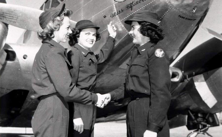 Three female pilots standing near their plane