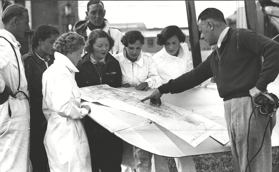Captain Duncan Davis giving female pilots and others tips while pointing at a map on the wing of a plant