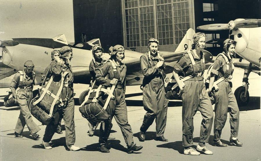 WASP pilots walking through a hanger carrying their parachutes