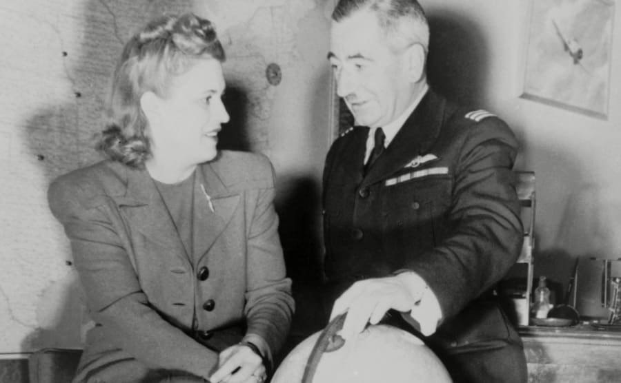 Jacqueline Cochran with Captain Norman Edgar looking at a globe while conversing