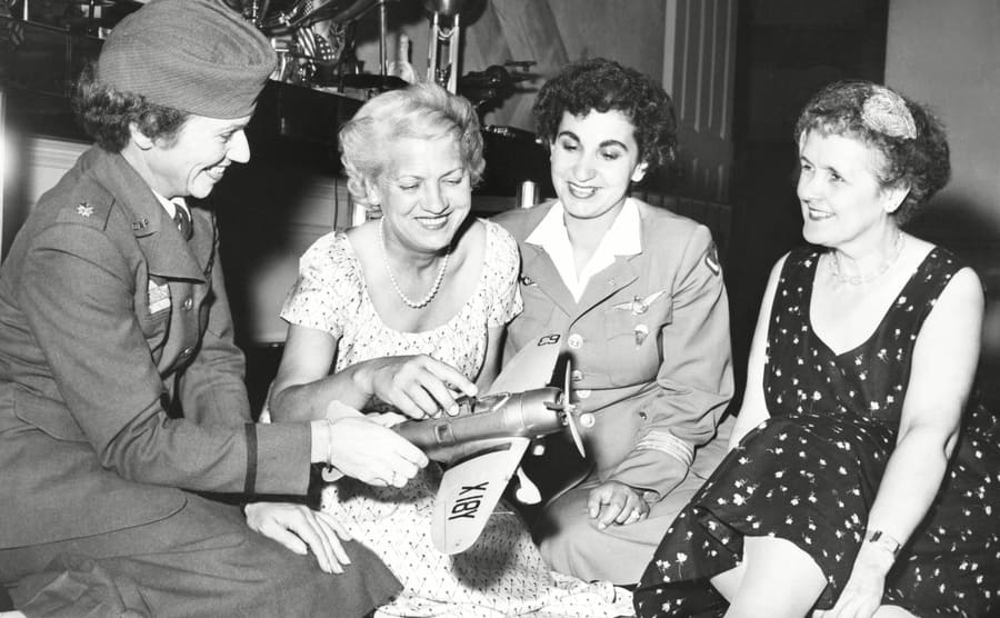 Jean Howard, Jacqueline Cochran, Edibe Subasu, and Ruth Nichols sitting together after dinner looking at a model airplane