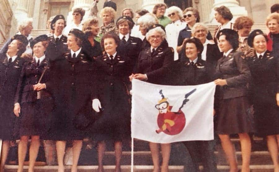 Members of WASP standing on steps holding a WASP flag