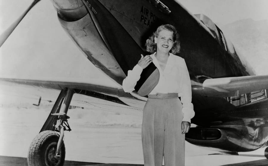 Jacqueline Cochran standing in front of her plant in a pants suit in 1948.