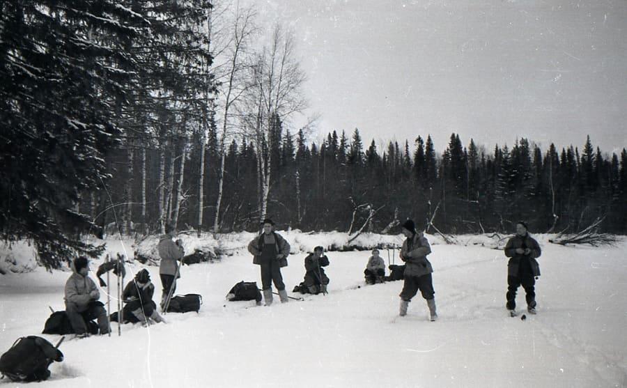 Zolotaryov, Kolmogorova, Slobodin, Doroshenko, Kolevatov, Dubinina, Thibeaux-Brignolle, and Dyatlov standing in the snow in front of a snow-covered forest