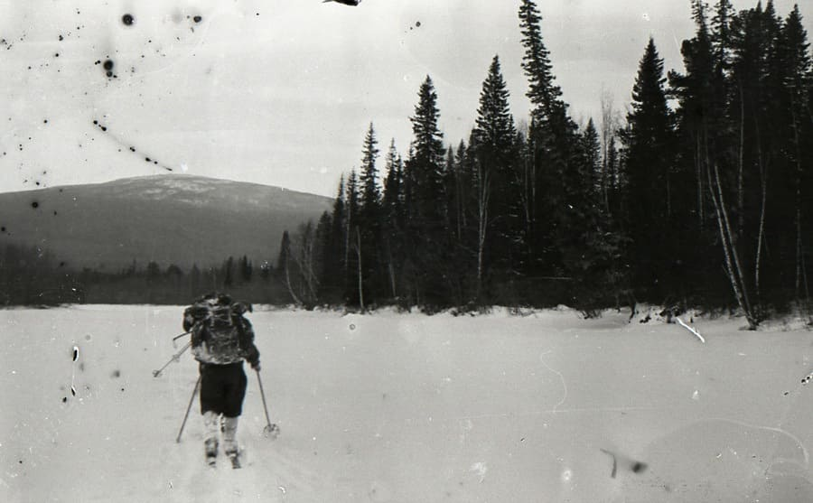 Hoy-Ekva Mountain in the distance with a hiker skiing across the open snowy field