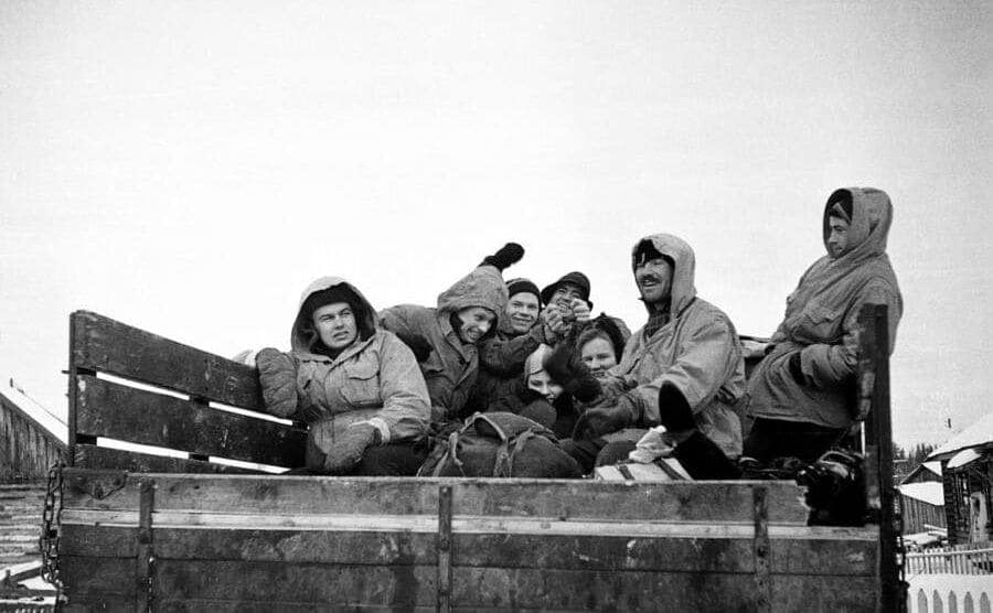 The boys in the back of a truck wearing winter gear and looking excited about the journey