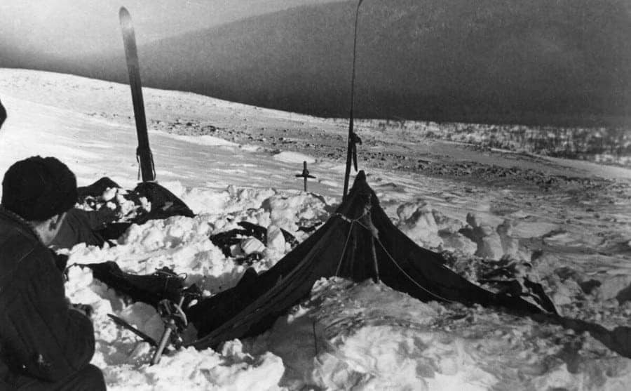 The tent covered in snow with rescuers investigating the situation