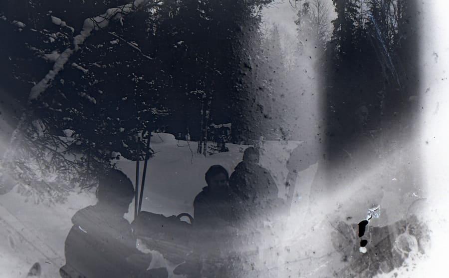 A photograph of Kolmogorova, Dubinina, Kolevatov, and Slobodin sitting around a fire