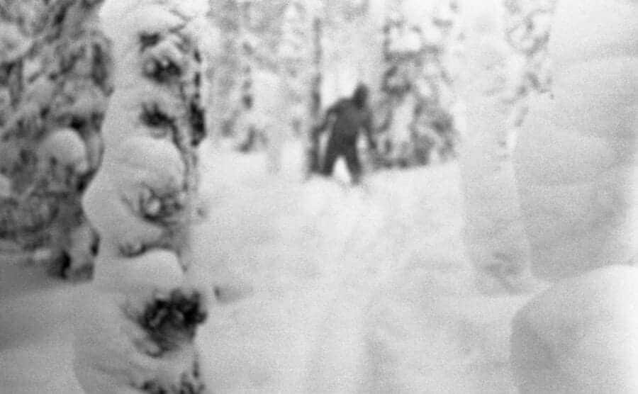 A photo of an unknown blurry man walking towards the camera in a snow-covered forest