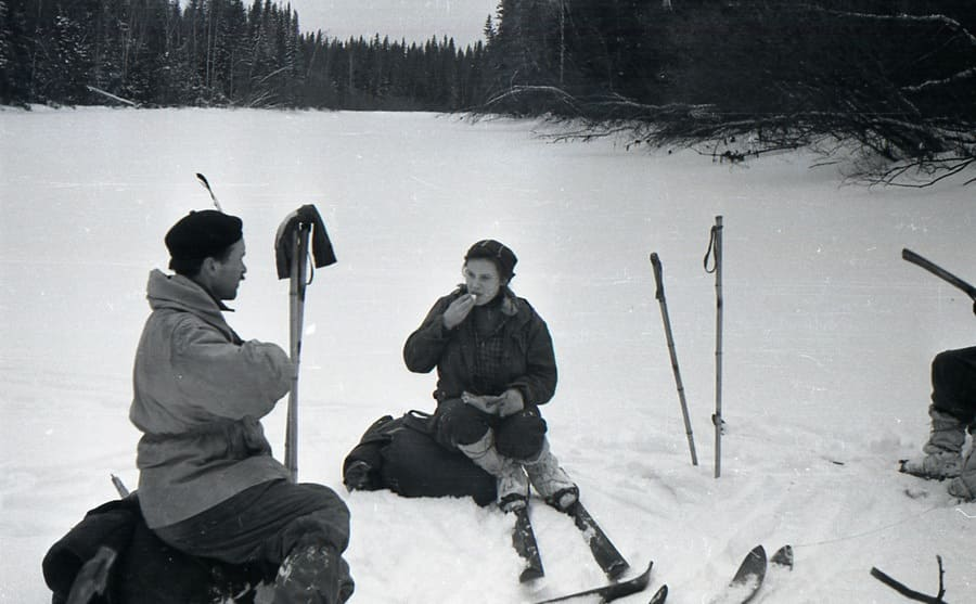 Zolotaryov and Kolmogorova chatting while sitting on their backpacks with their skis on
