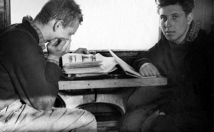 Igor Dyatov and Pyotr Bartolomey sitting at a table together reading through books