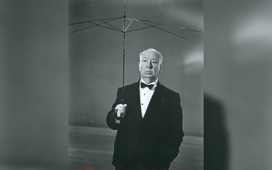 Alfred Hitchcock holding an umbrella