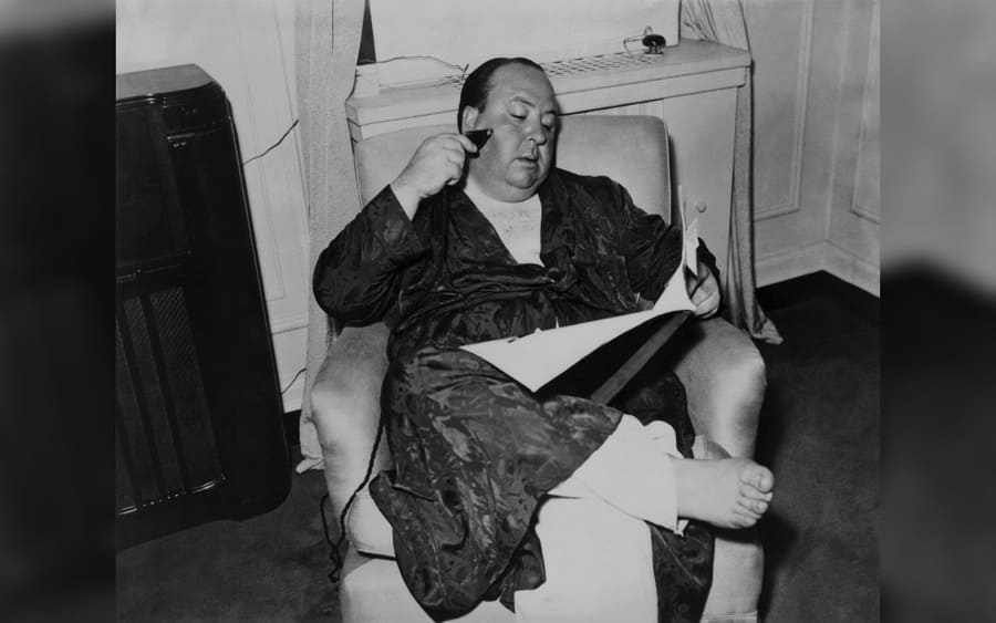 Alfred Hitchcock, seated in a recliner, shaving, and reading while in his pajamas and robe, 1938.