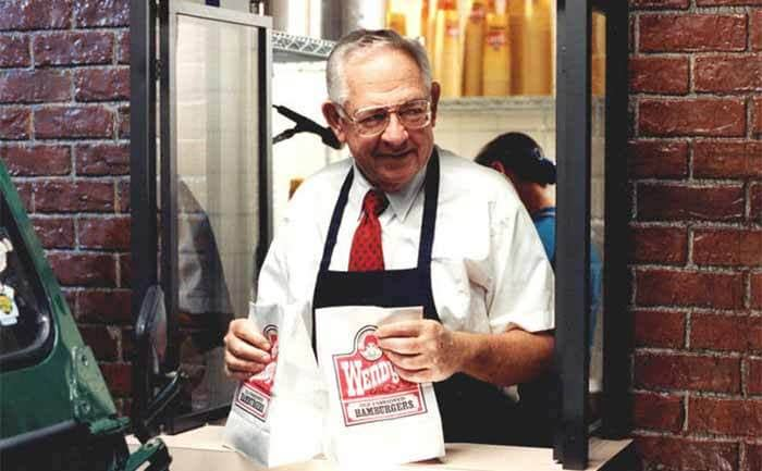 Dave Thomas standing in a Wendy's Drive Thru holding some to-go bags