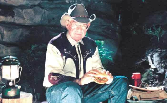 Dave Thomas sitting in the woods with a cowboy hat on, a lantern, and a thermos around him while he eats a burger