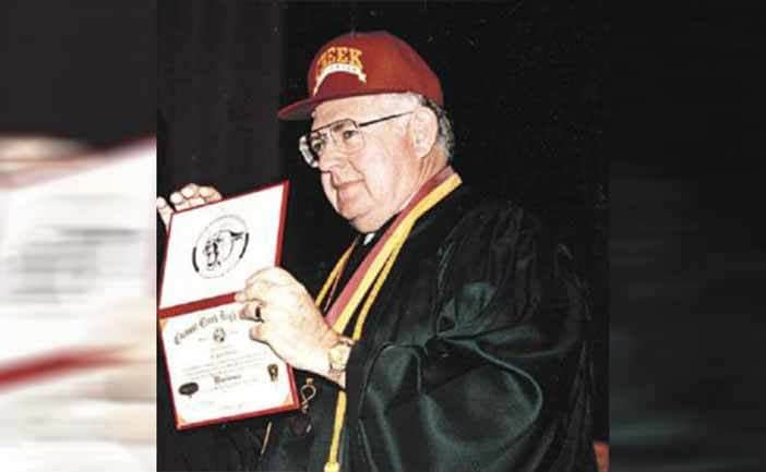 Dave Thomas holding his GED on stage
