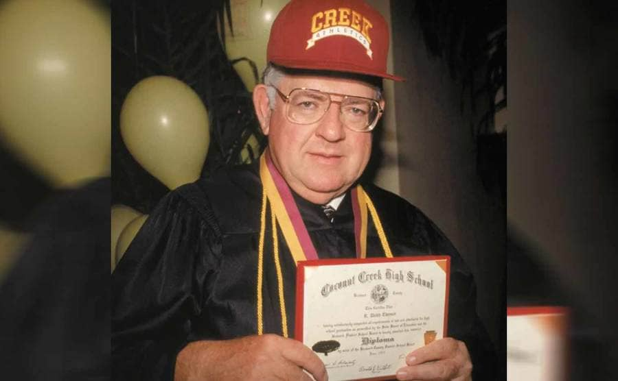 Dave Thomas holding his diploma and wearing a Creek Athletics baseball hat