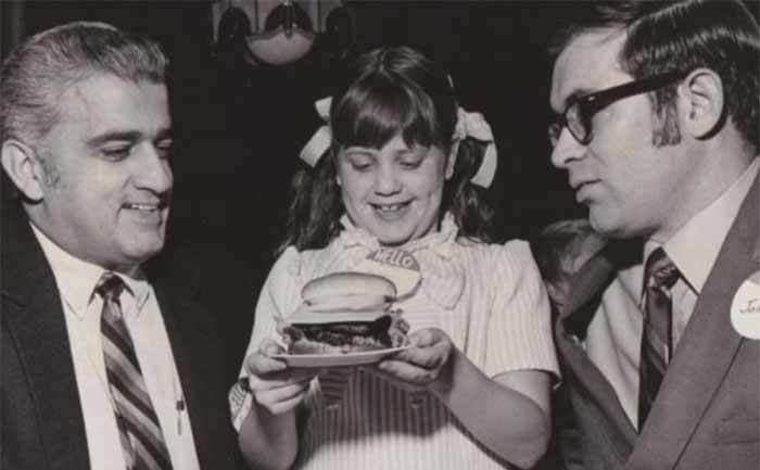 Melinda (nicknamed Wendy) holding a burger with Dave Thomas and another man