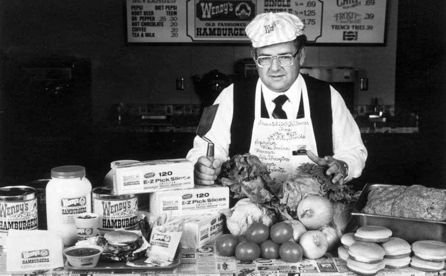 Dave Thomas standing in front of a countertop with different fresh ingredients for Wendy's burgers