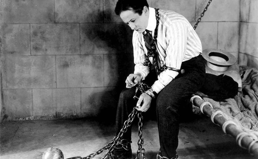 Harry Houdini in a jail cell with balls and chains attached to him