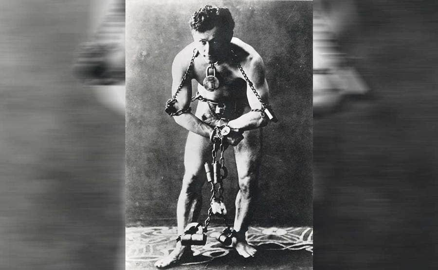 Harry Houdini trying to escape from chains and handcuffs