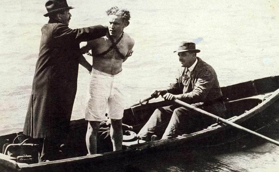 Houdini in a boat with handcuffs and chains on him