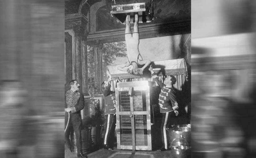 Houdini hanging by his feet above a water cell