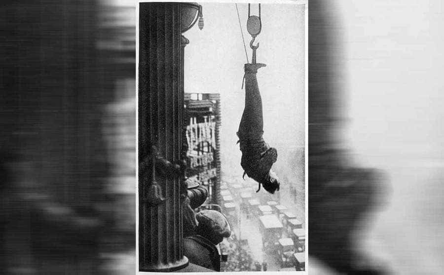 Houdini suspended from an NY skyscraper while wearing a straightjacket