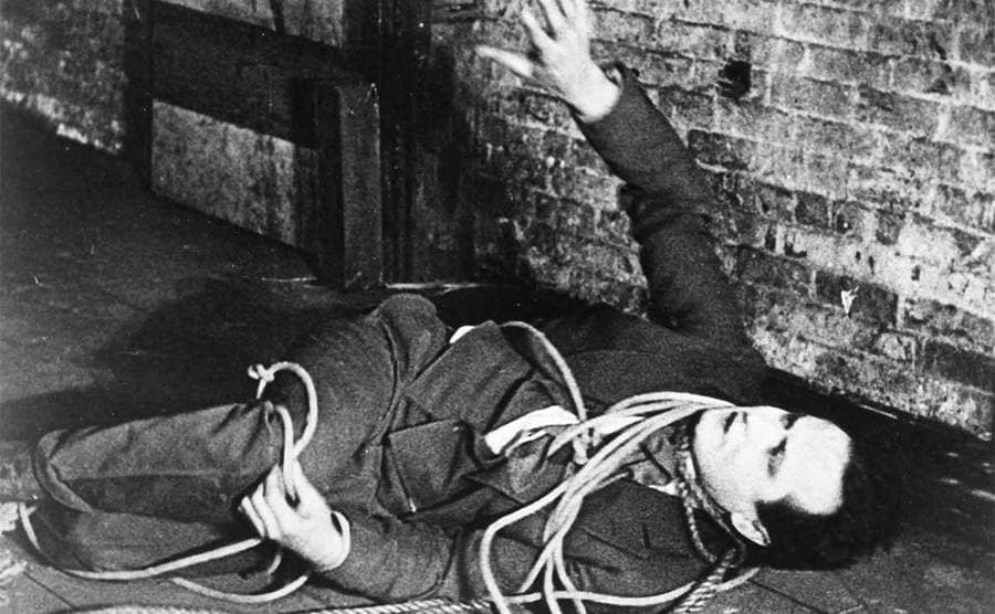 Harry Houdini lying on the floor covered in ropes with one hand in the air