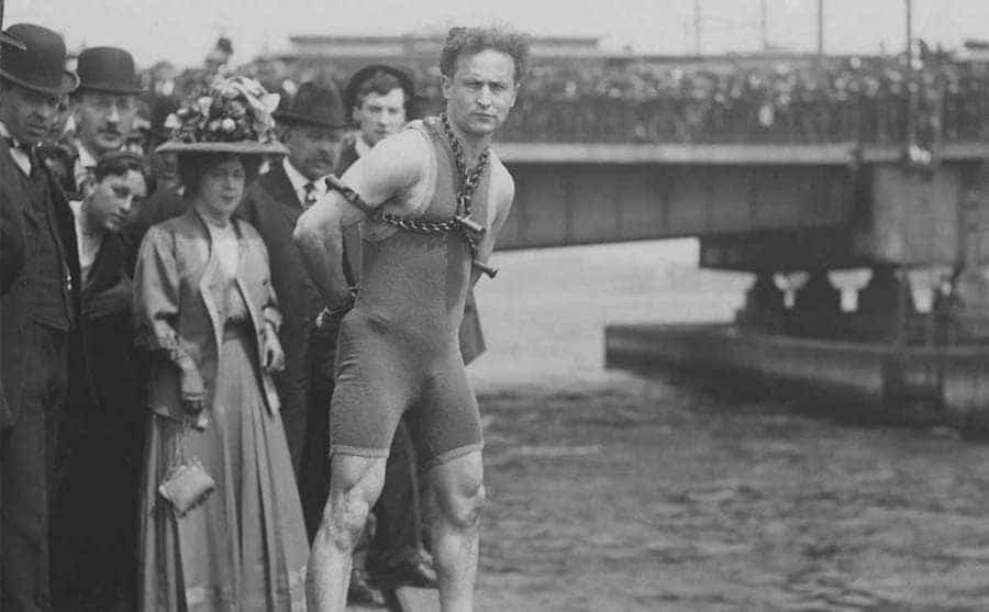 Harry Houdini standing with shakles on in front of a large body of water