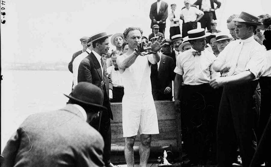 Harry Houdini surrounded by people handcuffed and legs shakled next to a body of water