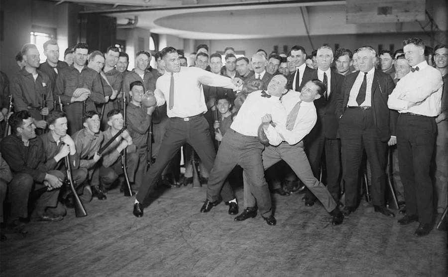 Houdini being held back while Jack Dempsey has his arm back ready to punch him in the gut