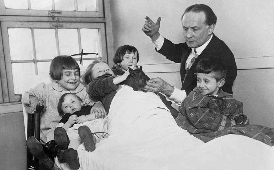 Harry Houdini performing magic with his rabbit in the hospital for sick children