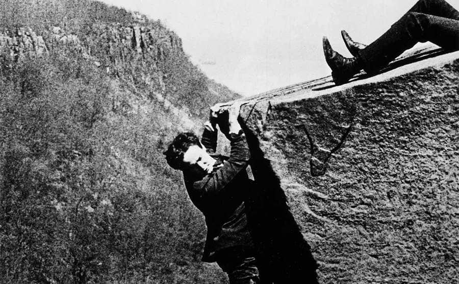 Houdini hanging from a ledge of a cliff