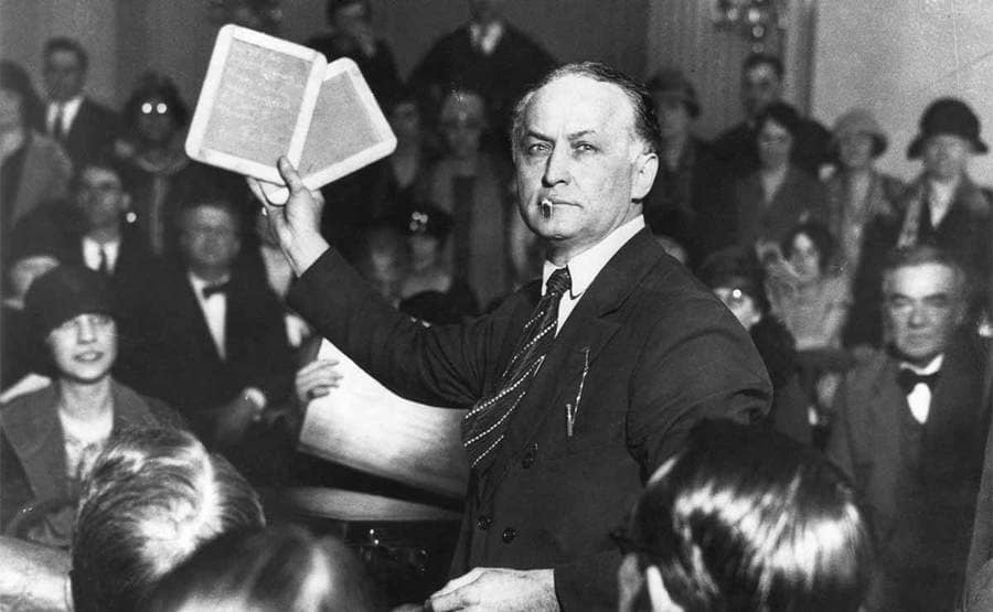 Harry Houdini in front of a senate committee holding up two rectangular items