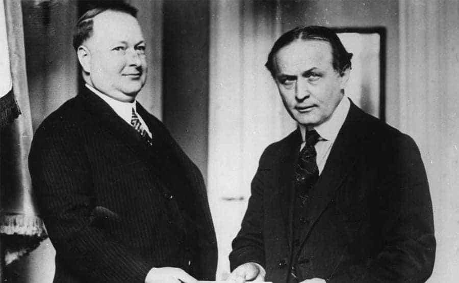 Harry Houdini handing another man a handful of bonds