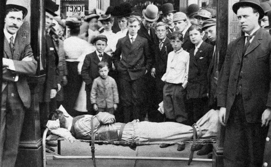 Harry Houdini lying in a bed tied up with onlookers gathered around
