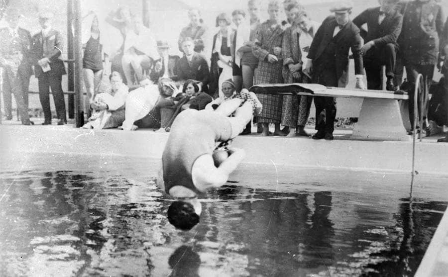 Houdini diving into a pool with chains on