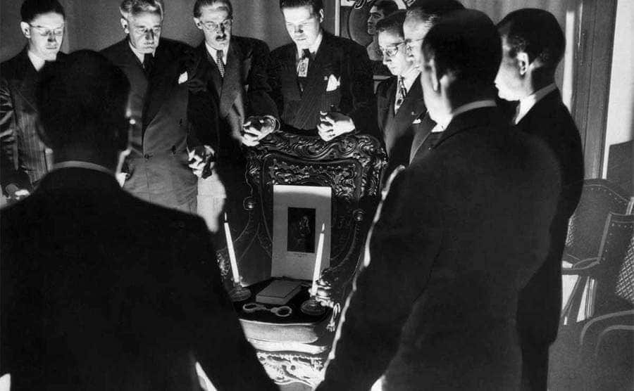 Magicians conducting a séance in attempt to contact the spirit of Harry Houdini with his handcuffs, a photograph, and a book placed on a chair in the center of their circle