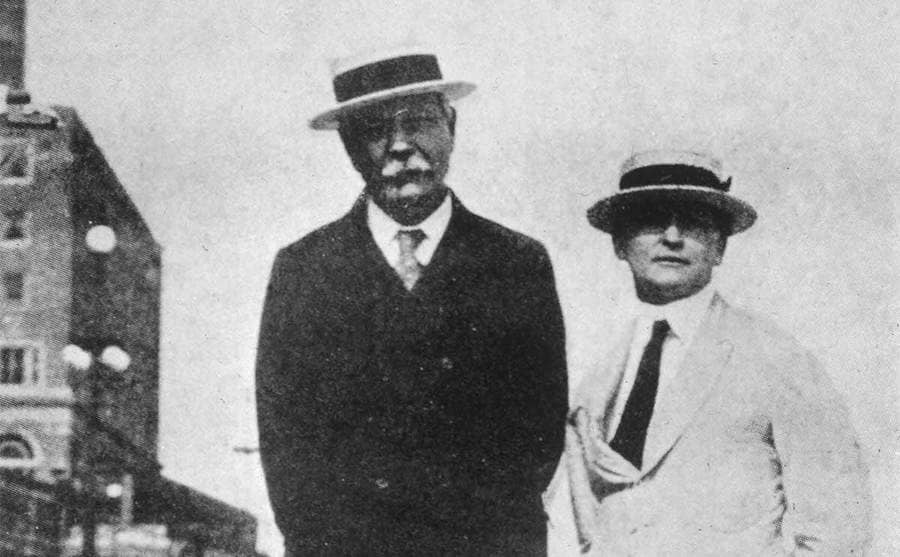Sir Arthur Conan Doyle and Harry Houdini standing outside in suits and top hats